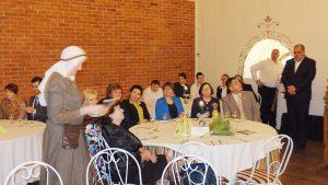 Renginio dalyviams dalijami ženkleliai jubiliejinei sueigai atminti
