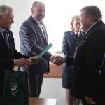 Savivaldybės mero pavaduotojas J. Kazla ir administracijos direktorius V. Kazlas sveikina policijos pareigūną R. Joniką.