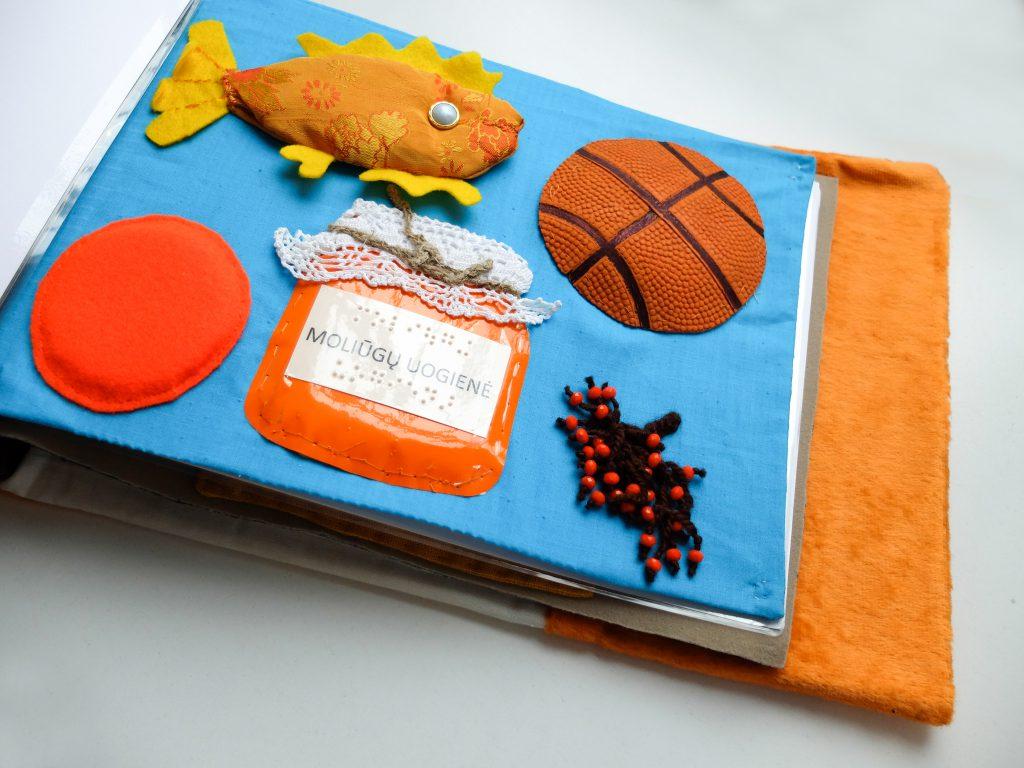 Iliustracija iš taktilinės knygelės Laimė yra lapė Oranžiniai dalykai