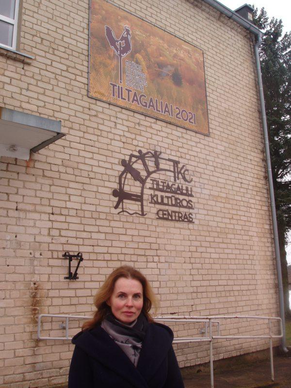Renata Kopūstienė prie kultūros centro, pasipuošusio mažosios Lietuvos kultūros sostinės lenta