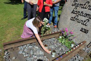 Pagėgių savivaldybės Vydūno viešosios bibliotekos direktorė Milda Jašinskaitė-Jasevičienė uždega žvakelę bei padeda gėlių prie paminklinio akmens tremtinių kančioms atminti / Ramutės Vaitkuvienės nuotr.