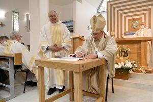Arkivyskupas Kęstutis Kėvalas pasirašo konsekracijos akte. Kairėje – klebonas kun. Antanas Gražulis SJ