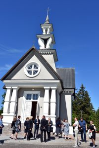 Minint 80-ąsias Rainių tragedijos metines grupė prie koplyčios susirinkusių svečių / Loretos Norvaišienės nuotr.